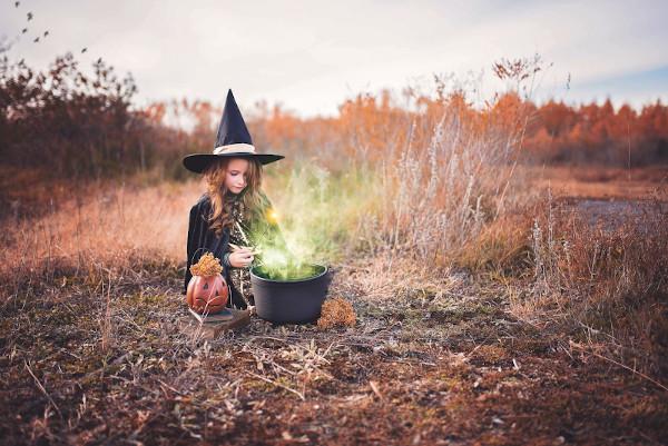 Ein Mädchen im Hexenkostüm sitzt vor einem Kessel aus dem grüner Dampf aufsteigt