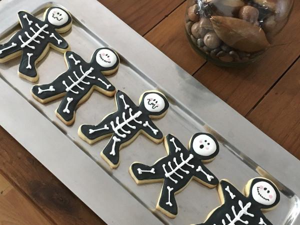 Auf einem Silbertablett liegen Kekse, die als Skelette dekoriert wurden