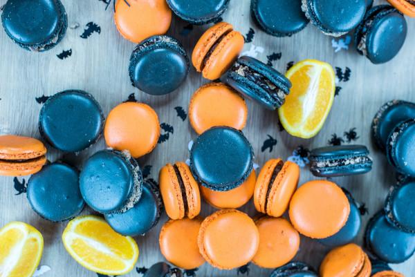 Orangene und schwarze Macarons liegen auf einer Holzplatte zusammen mit Zitronenstücken und kleinen Papier-Fledermäusen