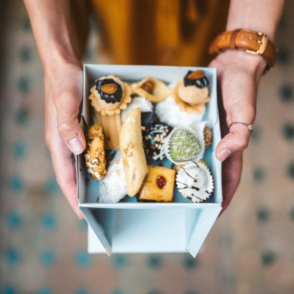 Eine Kiste gefüllt mit verschiedenen Plätzchen wird in zwei Händen gehalten und präsentiert
