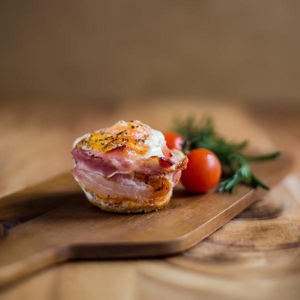 Ein Omlette-Muffin mit Bacon am Rand und Tomaten daneben liegt auf einem Holzbrett