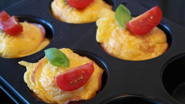 In einer Muffinform sind Omlette-Gebäcke mit Tomaten und Basilikum drapiert