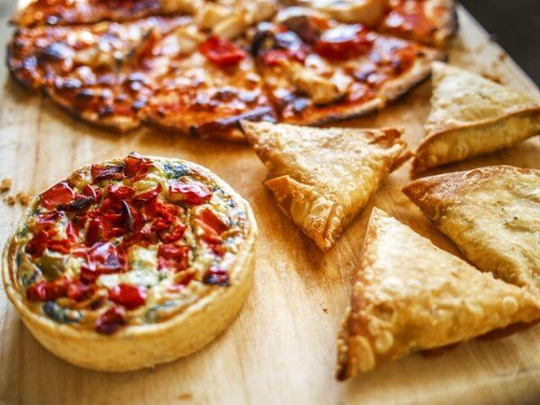 Auf einem Holzbrett liegen nebeneinander eine kleine Quiche, eine Pizza und gefüllte Blätterteigecken