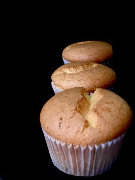 Hintereinander vor einem schwarzen Hintergrund stehen drei Muffins