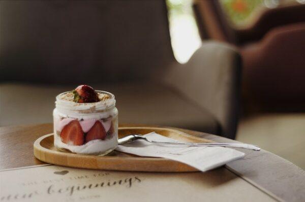 Auf einem Holztablett steht ein Kuchen im Glas mit Erdbeeren und einer Cremefüllung