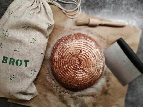 Ein Brot liegt neben einem Jutebeutel mit der Aufschrift Brot