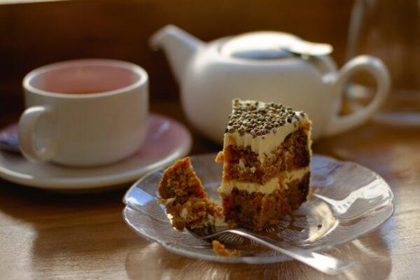 Ein Stück Kuchen mit Hanfsamen dekoriert steht auf einem Teller. Daneben eine Kanne und eine Tasse Tee.