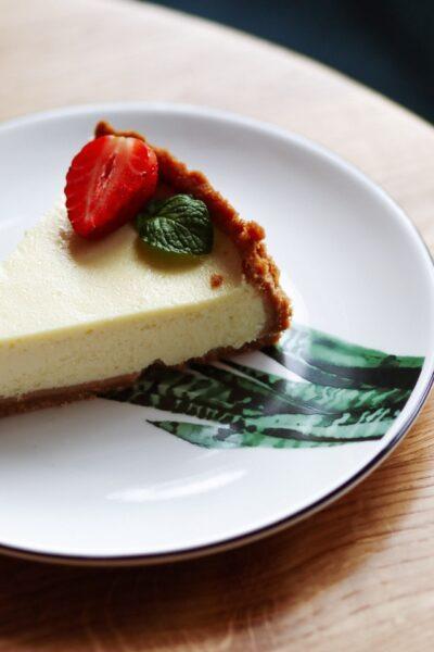 Auf einem Teller liegt ein Stück Käsekuchen mit Minze und Erdbeeren verziert