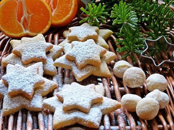 Neben einigen sternförmigen Plätzchen liegen Macadamias, Orangen und Tannenzweige