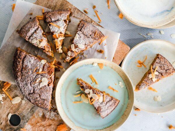Auf einem Holzbrett und einigen Tellern sind einige Kuchenstücke mit Mandeln dekoriert verteilt