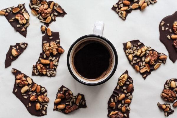 Neben einer Kaffeetasse liegen Stücke einer Nussschokolade