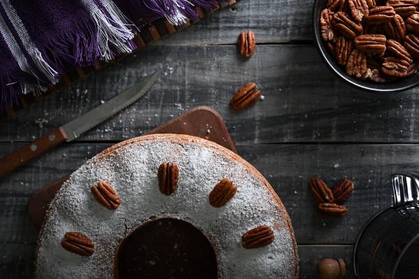 Ein Königskuchen mit Puderzucker bestreut wurde mit Pekannüssen dekoriert