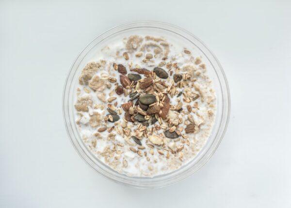 In einer Glasschüssel befindet sich ein Müsli in Milch mit Nüssen und Kernen darin