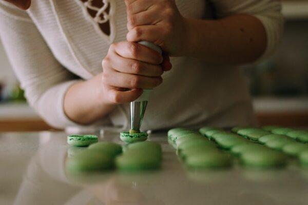 Eine Person füllt grüne Macarons