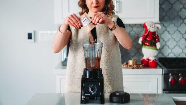 Eine Frau schüttet etwas Kakaopulver in einen Standmixer