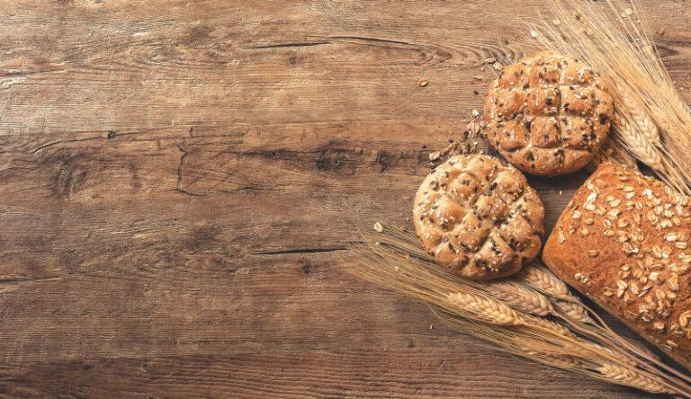 Auf einem Holzuntergrund liegen zwei Brötchen, ein Brot und etwas Getreide