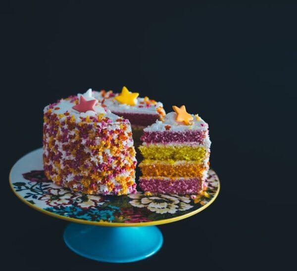 Ein Kuchen dessen Schichten in unterschiedlichen Rot- und Gelbtönen eingefärbt wurde, ist auf einer Etagere serviert wurden