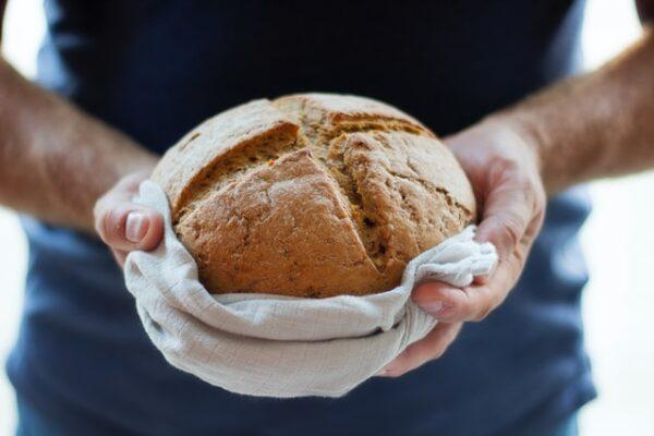 Jemand hält ein Brot mit einem Küchentuch ringsherum in der Hand