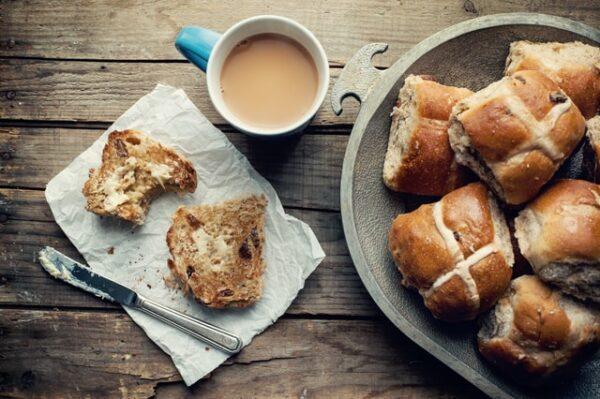 Auf einem Teller liegen Hot Cross Buns und daneben eine Tasse Kaffee und ein aufgeschnittenes Brötchen