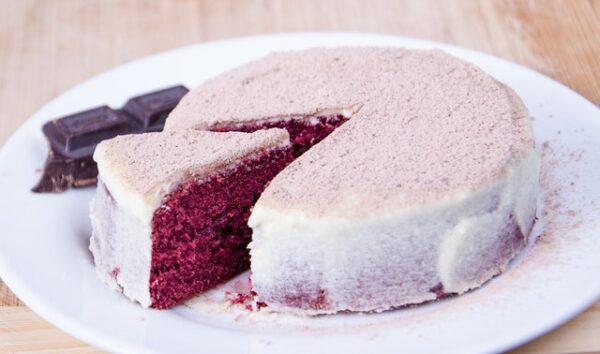 Ein Kuchen, dessen Teig pink eingefärbt ist und der mit Zuckerguss dekoriert wurde, wurde angeschnitten