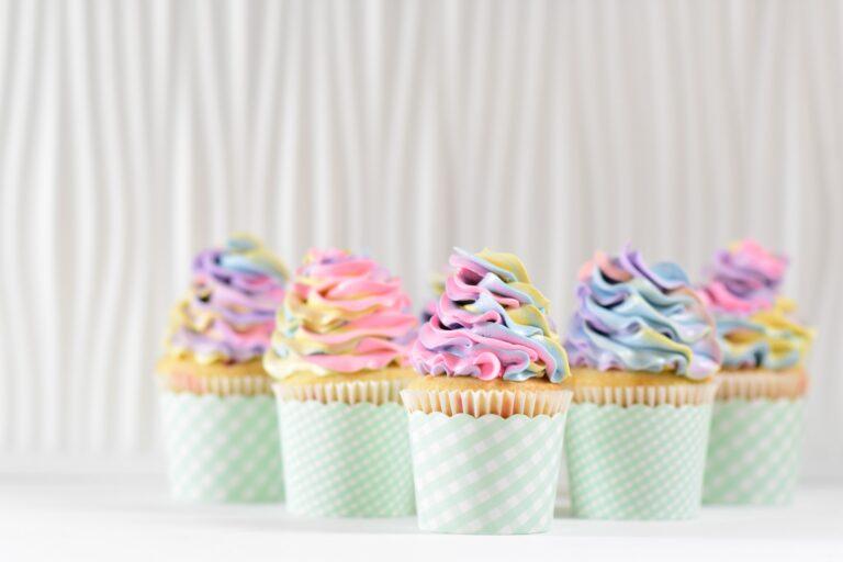 Fünf Cupcakes mit einem bunten Frosting stehen vor einem weißen Vorhang