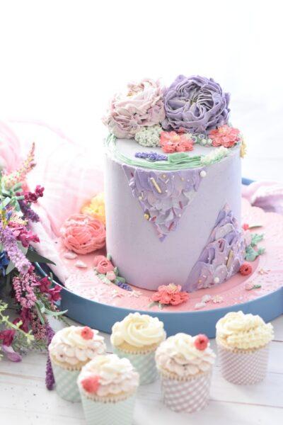 Ein Kuchen und Cupcakes wurden mit eingefärbter Buttercreme dekoriert