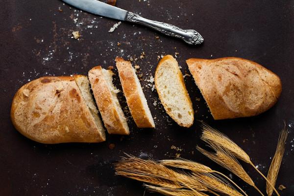 Ein angeschnittenes Baguette neben dem ein Messer und etwas Getreide liegt