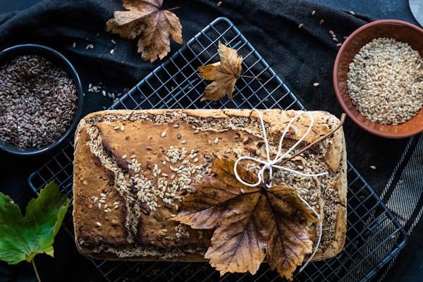 Rund um ein Brot liegen Sesamkerne und getrocknete Blätter