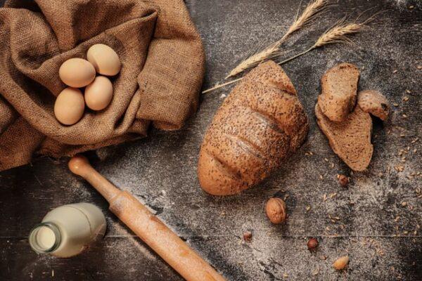 Neben einem Brot liegen Eier, Milch und einige Getreidehalme