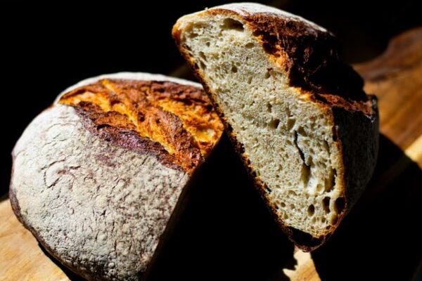 Ein angeschnittenes Brot liegt auf einer Holzfläche