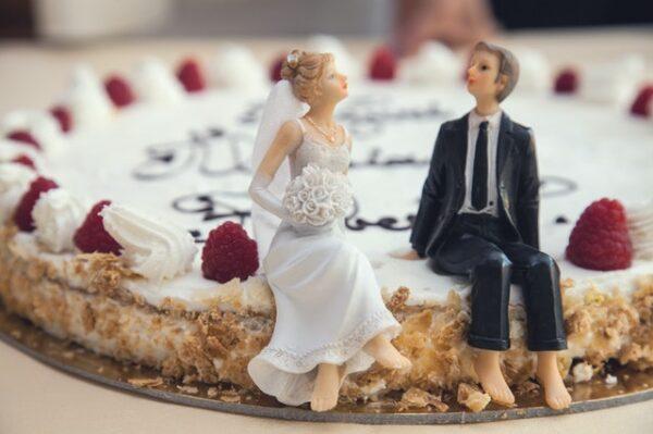 Ein flacher Hochzeitskuchen an dessen Ran zwei Figuren sitzen