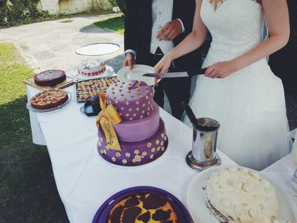 Ein Ehepaar schneidet einen Hochzeitskuchen an