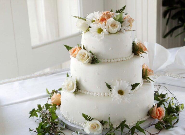 Eine weiße Hochzeitstorte dekoriert mit Fondant und einer Menge Blumen steht auf einem Tisch