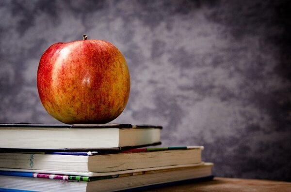Ein Apfel liegt auf einem Stapel Bücher