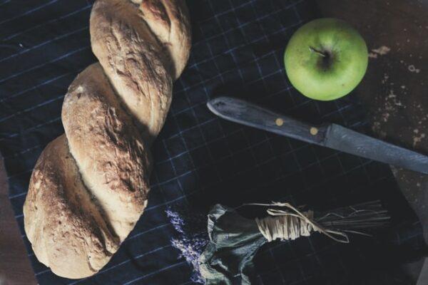 Ein gedrehter Brotzopf liegt neben einem grünen Apfel