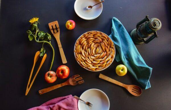 Ein Apfelkuchen ist von verschiedenen Küchenutensilien und einigen Zutaten umgeben