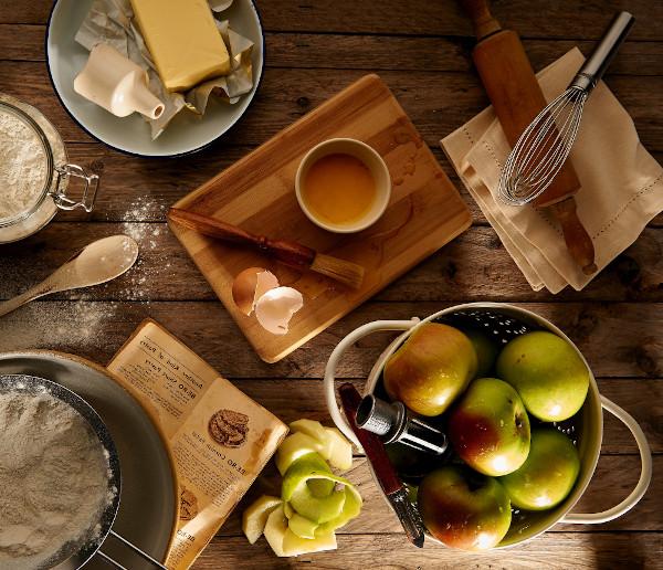 Auf einem Tisch stehen unterschiedliche Backzutaten, darunter auch Äpfel