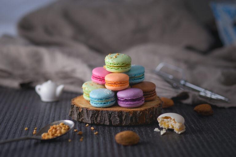 Ein Stapel aus bunten Macarons liegt auf einer Baumstammscheibe