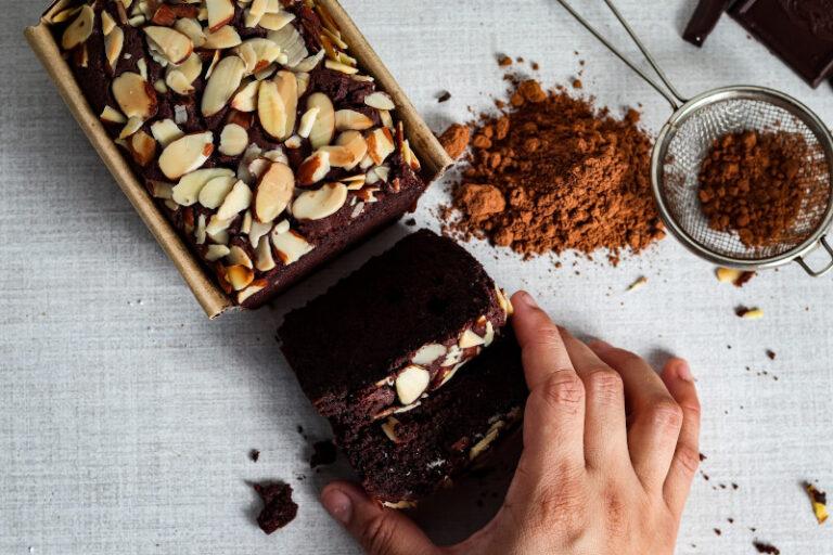 Jemand nimmt sich ein Stück eines schokoladigen Kuchens in Kastenform, welcher mit Mandelsplittern dekoriert wurde