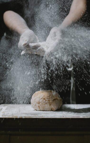 Hände bestäuben einen Brotteig mit Mehl