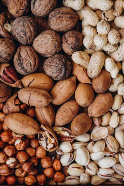 Viele Nüsse (Mandeln, Erdnüsse, Haselnüsse, Walnüsse) liegen auf einem Haufen