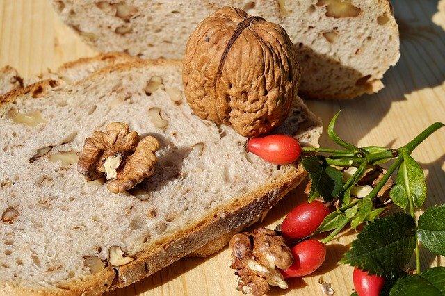 Eine Brotscheibe mit Walnüssen und Hagebutten liegt auf einem Holztisch