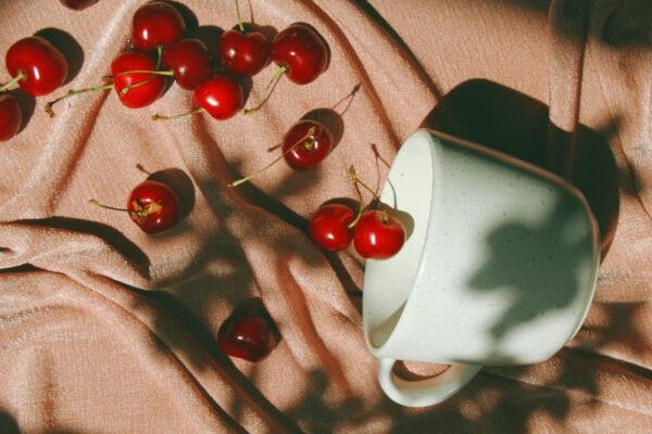 Neben einer Tasse liegen einige Kirschen