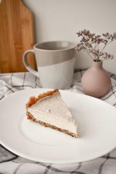 Ein Stück Kuchen mit Frischkäsefüllung, das neben einer Tasse und Vase steht
