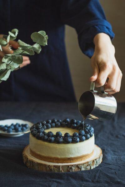 Jemand gießt Sirup über einen Kuchen verziert mit Blaubeeren