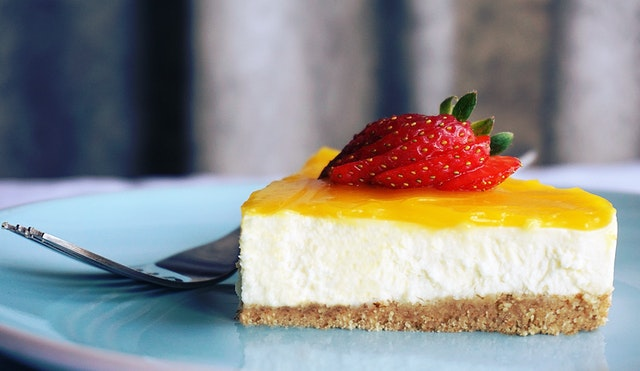 Ein Stück No Bake Kuchen mit Erdbeere und einer Schicht aus passierten Orangen als Verzierung