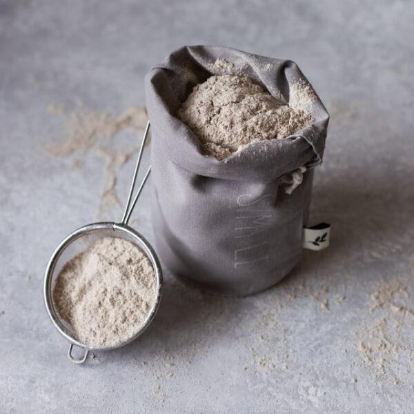 Neben einem Sack Mehl liegt ein kleines Sieb, welches ebenfalls mit dem Pulver gefüllt ist