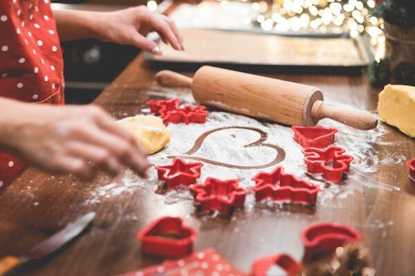 Auf einem Holztisch werden mit roten Ausstechförmchen Plätzchen gebacken. In das Mehl hat jemand ein Herz gemalt