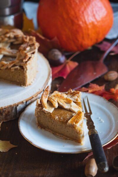 Ein Stück Kürbiskuchen liegt auf einem Teller neben einer Gabel. Im Hintergrund der Rest des Kuchens und herbstliche Dekorationen.