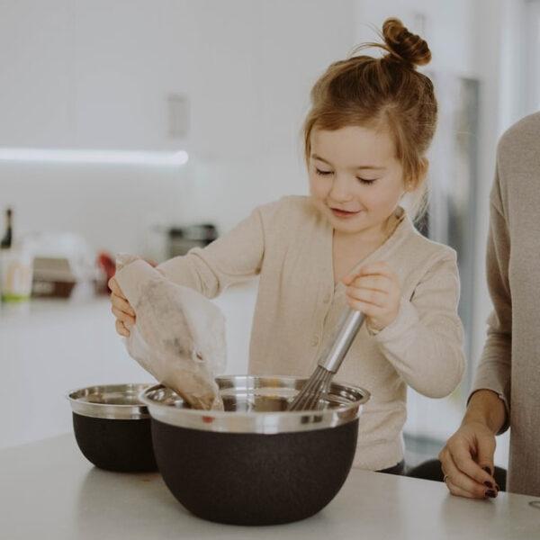 Ein kleines Kind rührt Zutaten in einer Schüssel zusammen